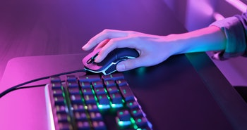 close up of pro cyber sport gamer play game with RGB keyboard and mouse