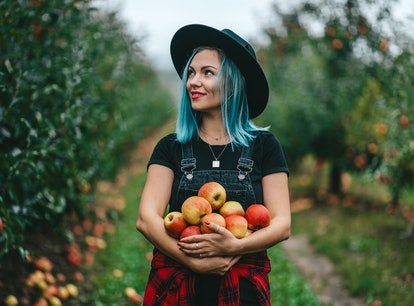 Blue haired woman picked up a lot of ripe red apple fruits in October 2021, the best month for her z...