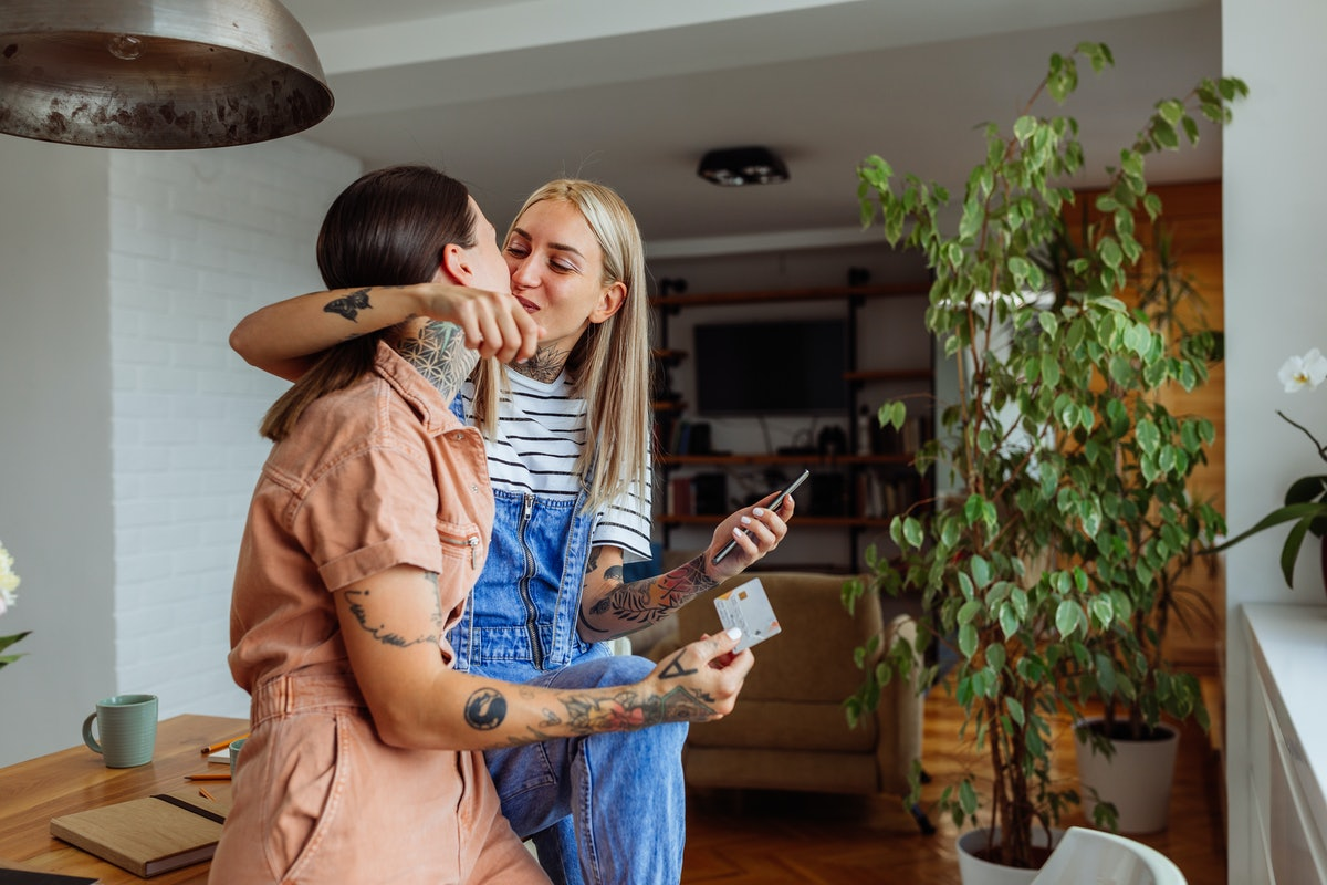Young affectionate lesbian couple Instagramming and kissing at home.