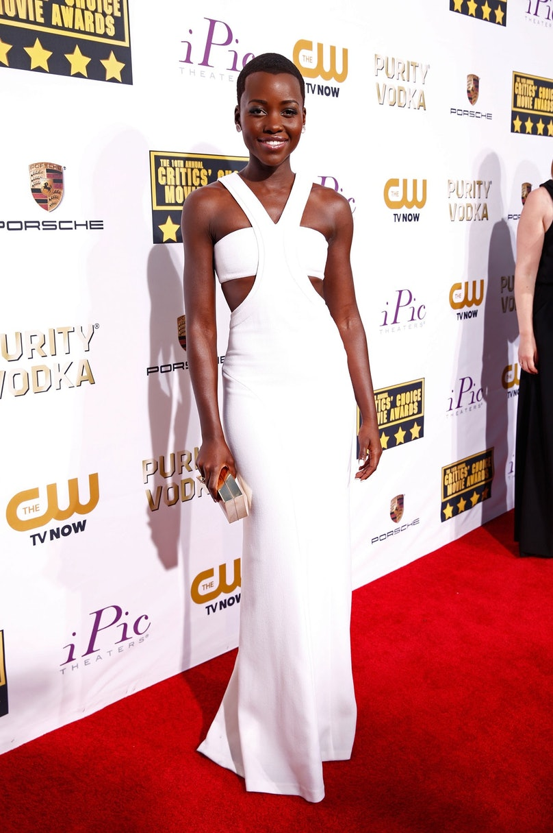 Following her red carpet hit at the Golden Globes, Nyong'o chose a similarly dramatic take on a simple silhouette for the Critics' Choice Awards. The combination of her white [Calvin Klein Collection](http://www.wmagazine.com/fashion/2013/12/francisco-costa-10-years-calvin-klein/) dress, [Paul Andrew](http://www.wmagazine.com/people/insiders/2013/07/paul-andrew-shoe-designer/) shoes, and Kimberly Macdonald jewelry was simply stunning.      Photo by Getty Images