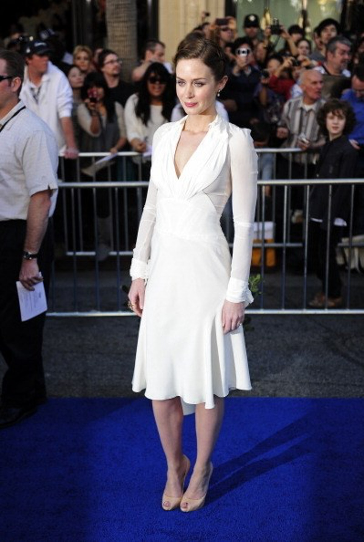 Emily Blunt in a white shirt dress.