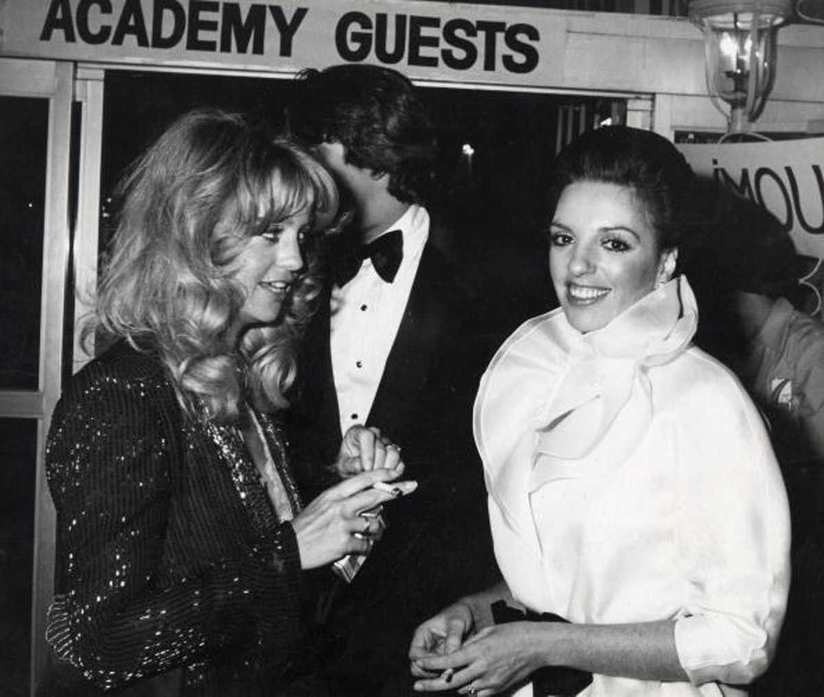 Goldie Hawn, Liza wears high collared white blouse that is cinched at the waist with a black bow.