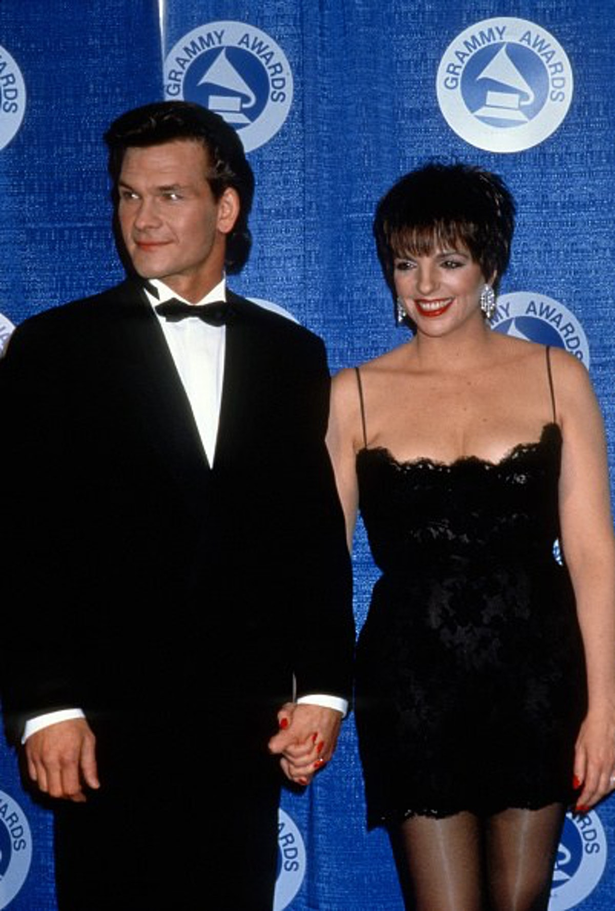 Liza in a form-fitting short black spaghetti strap dress