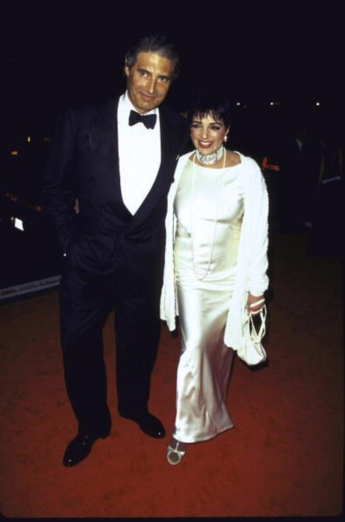 Liza wears  a white silk gown with matching white stole.
