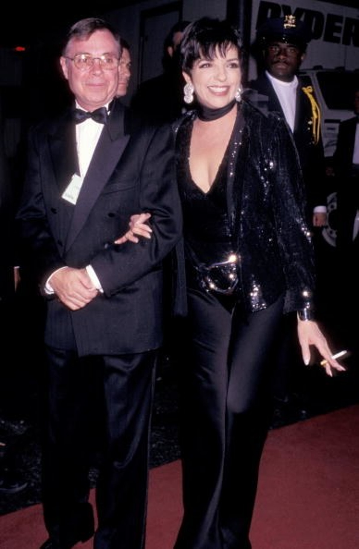 Liza wears all black look with deep cut top, wide legged pants, and a sequin blazer