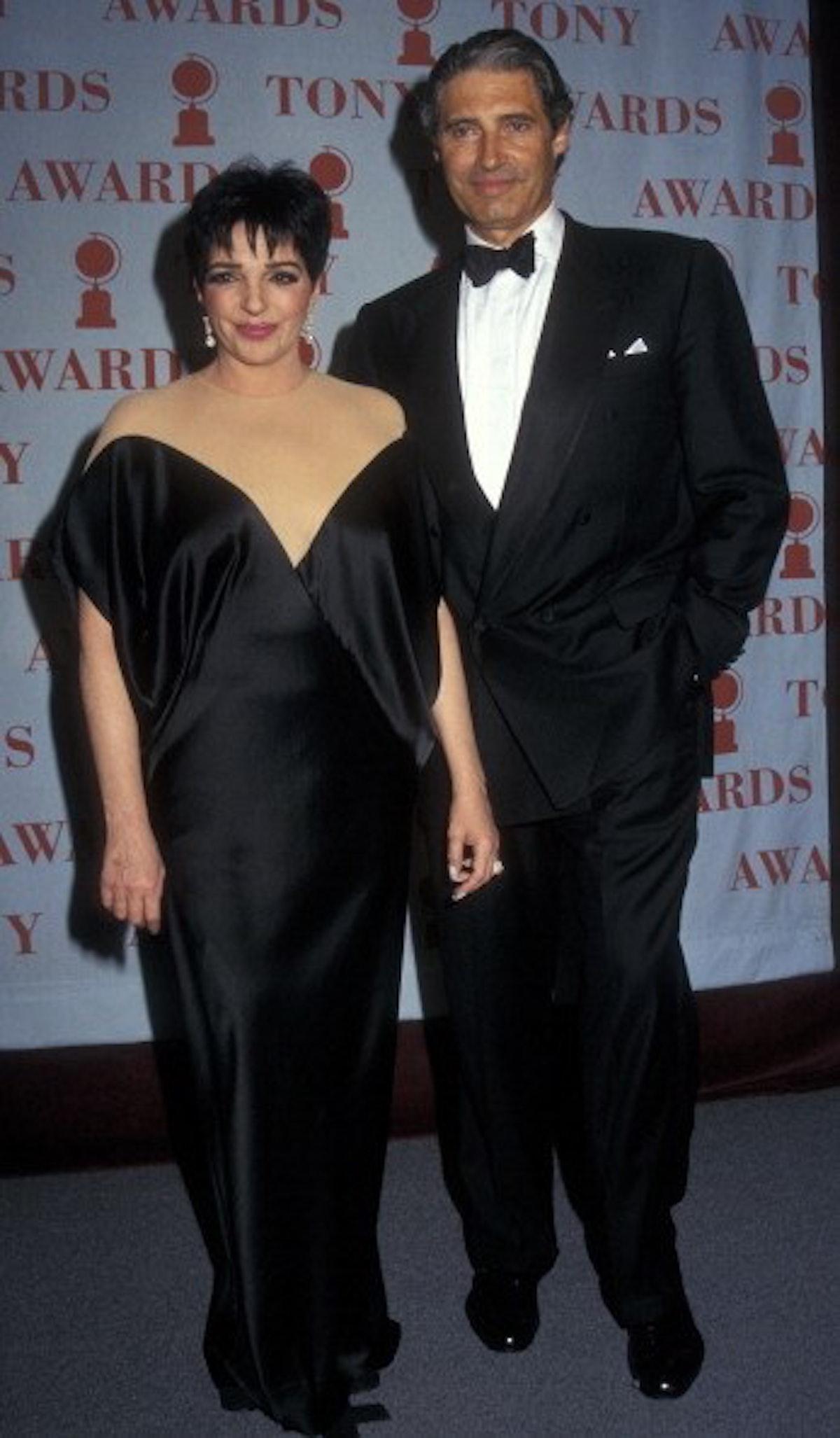 Liza  wears a simple off-the-shoulder black silk dress.