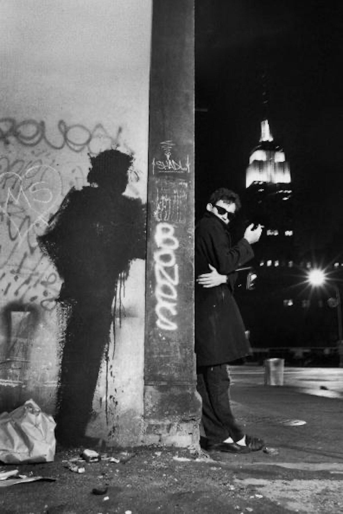Artist Richard Hambleton outside at night with one