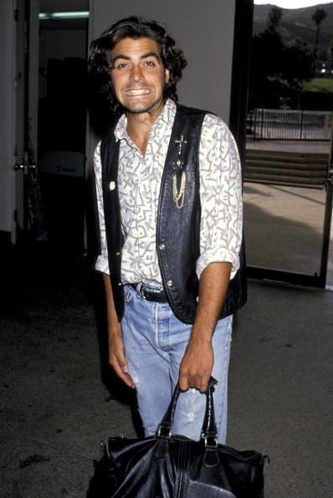 George Clooney with long hair and a black leather vest
