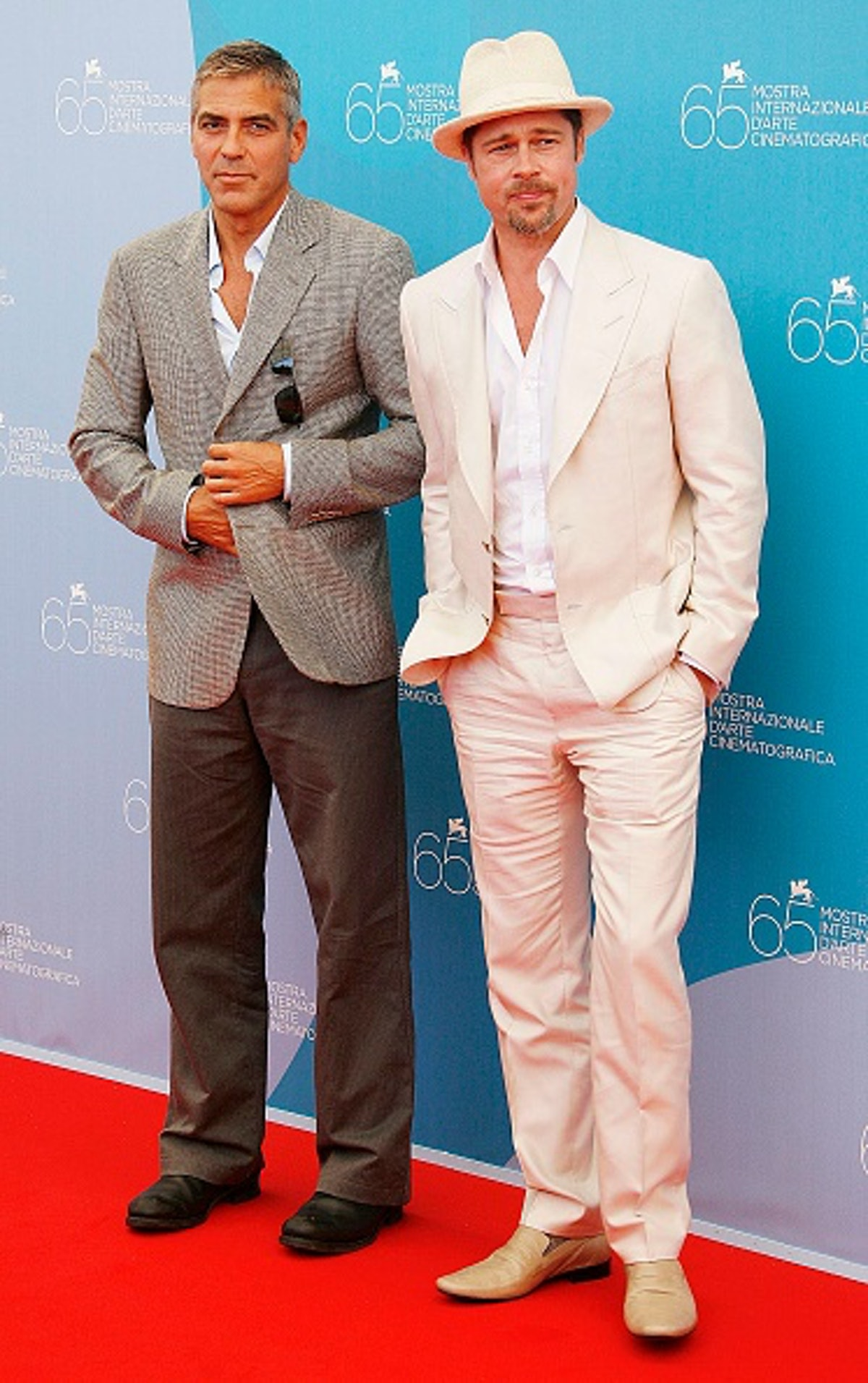 George wearing an Italian style gray suit and Brad Pitt in a cream suit