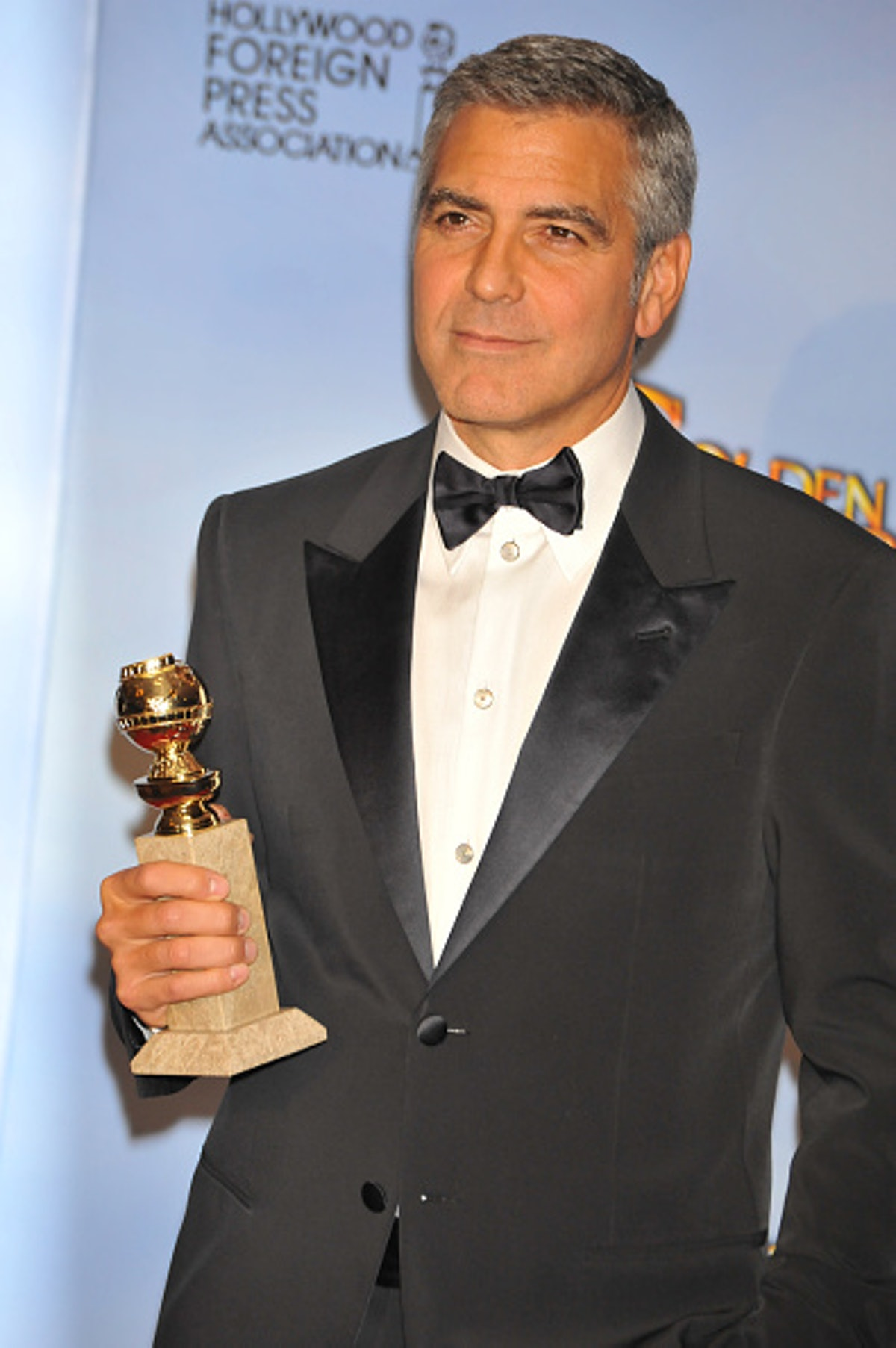 George in a tux holding his Golden Globe
