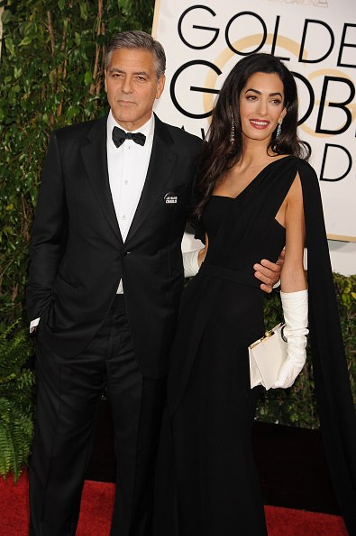 George in a black tux, Amal in a black gown and white gloves