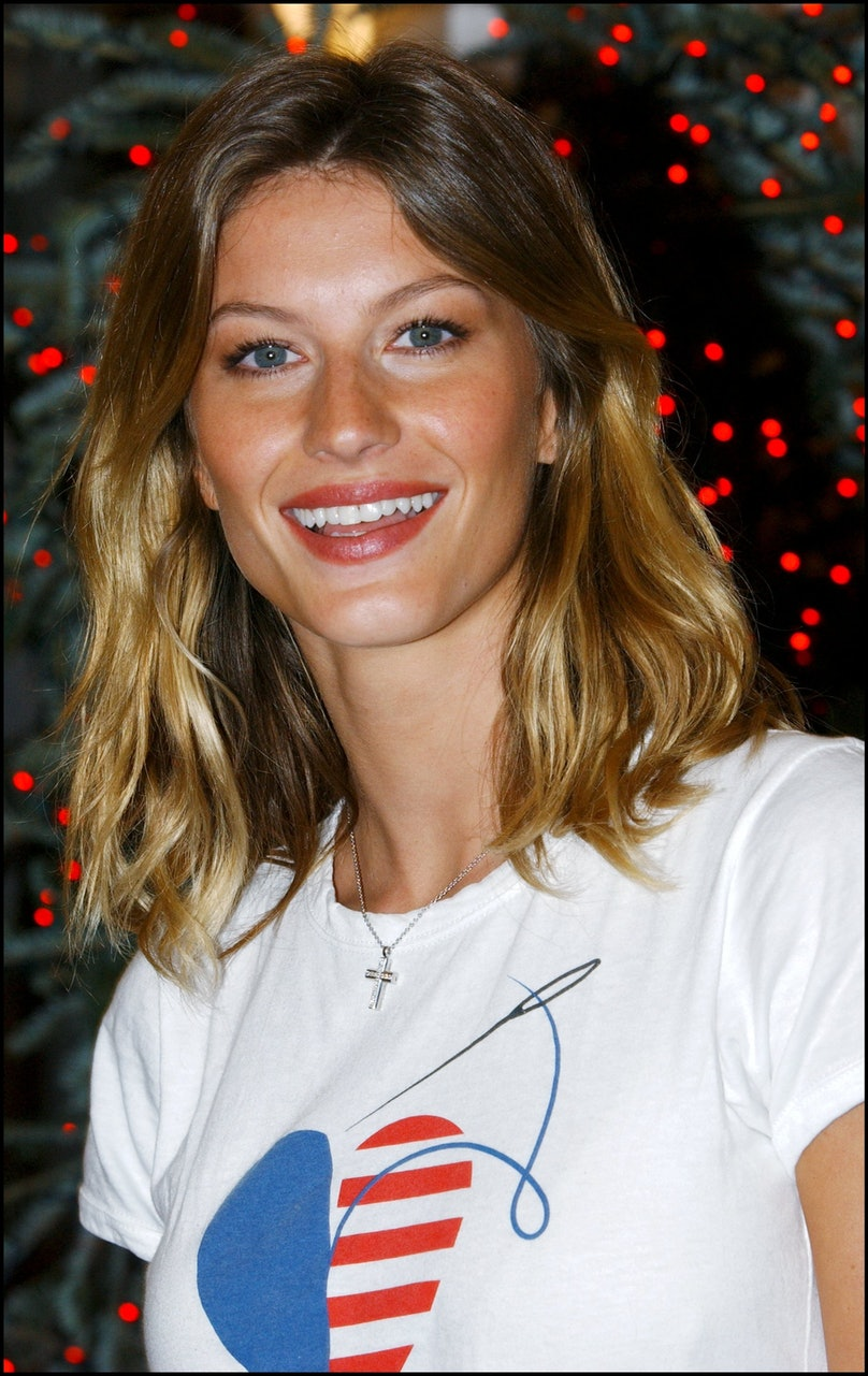 "Girl friend of Leonardo Dicaprio, supermodel Gisele Bundchen autographs December cover of Vogue, featuring photo of her wearing the CFDA/Vogue ""Fashion for America"" fund raiser T-shirt for the Twin Towers Fund in New York, United States on December 11, 20"