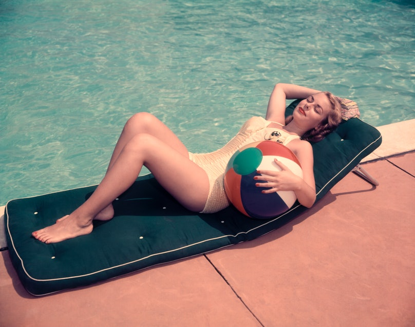 Woman Sun Bathing On Green Mat By Edge Side Of Pool Water Recline Holding Beach Ball By Her Side Relax.
