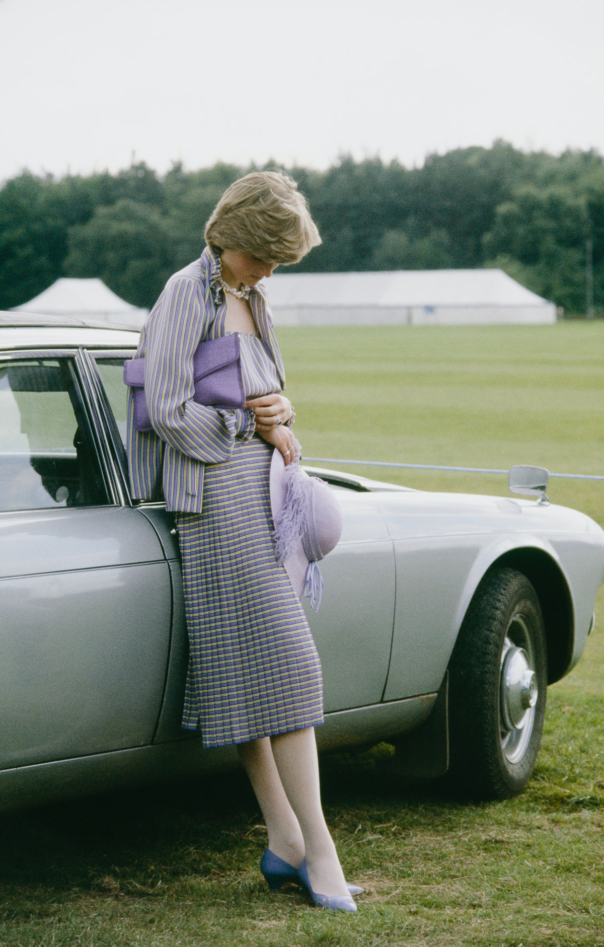 Diana Spencer wearing a lilac ensemble and staring at the ground
