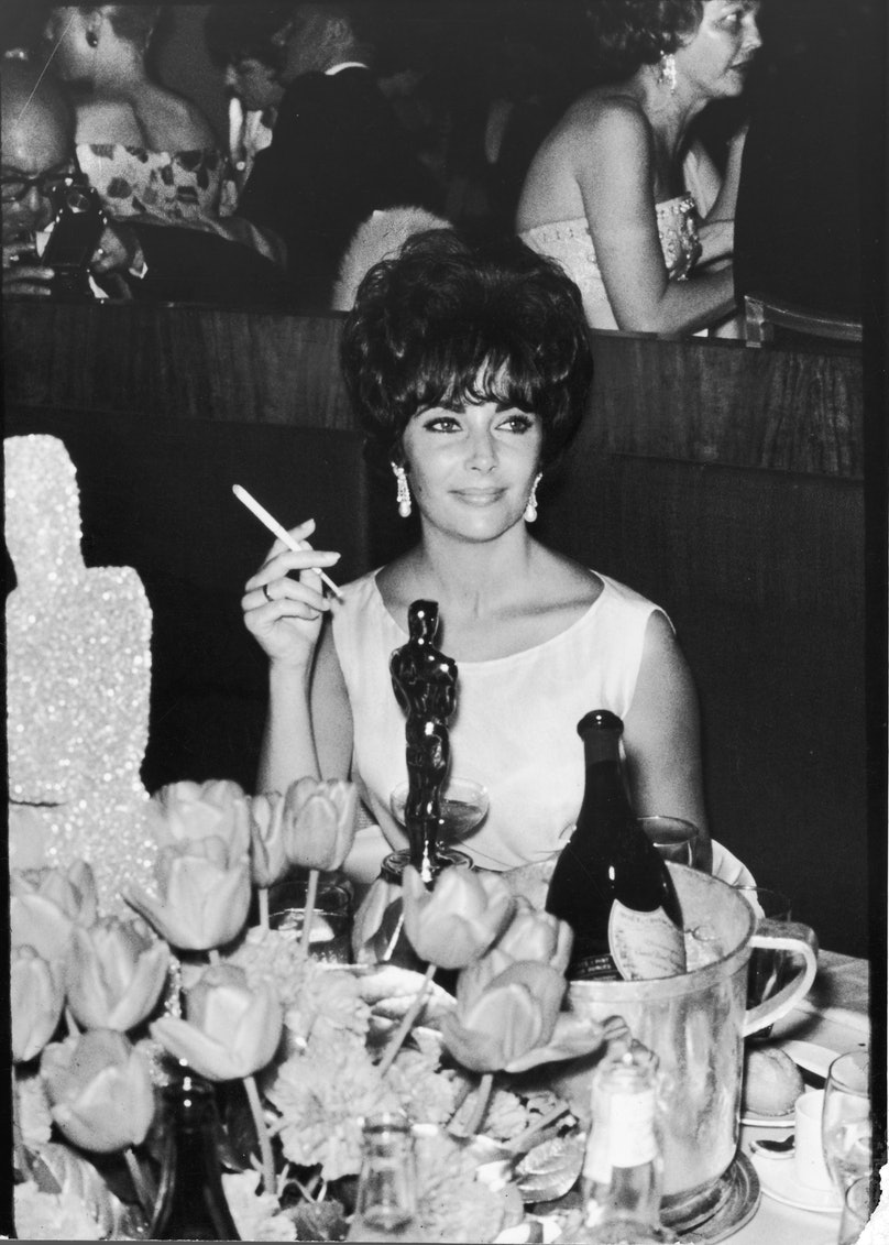 Actress Elizabeth Taylor at Hollywood party after winning oscar, which is on table in front of her.