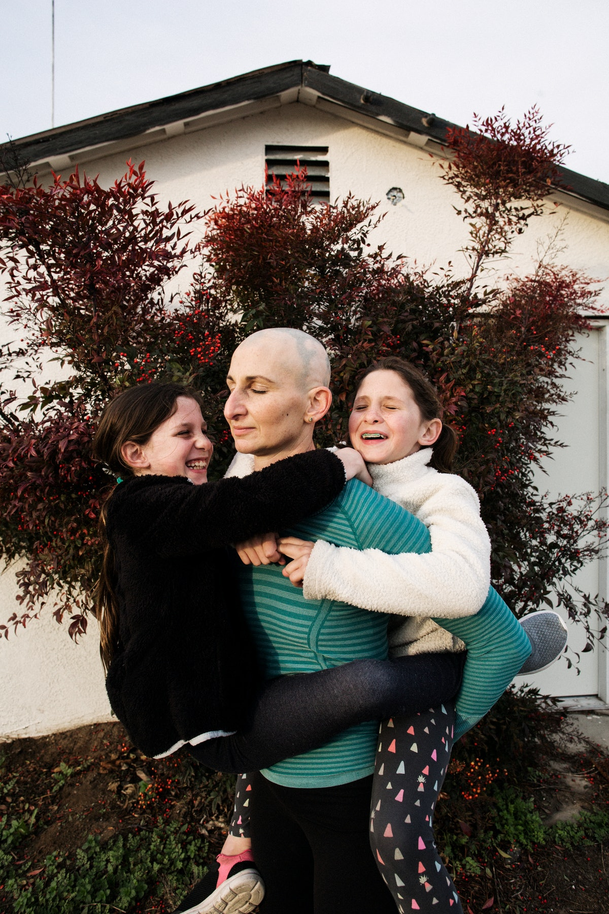 a portrait of a mother with her twin daughters