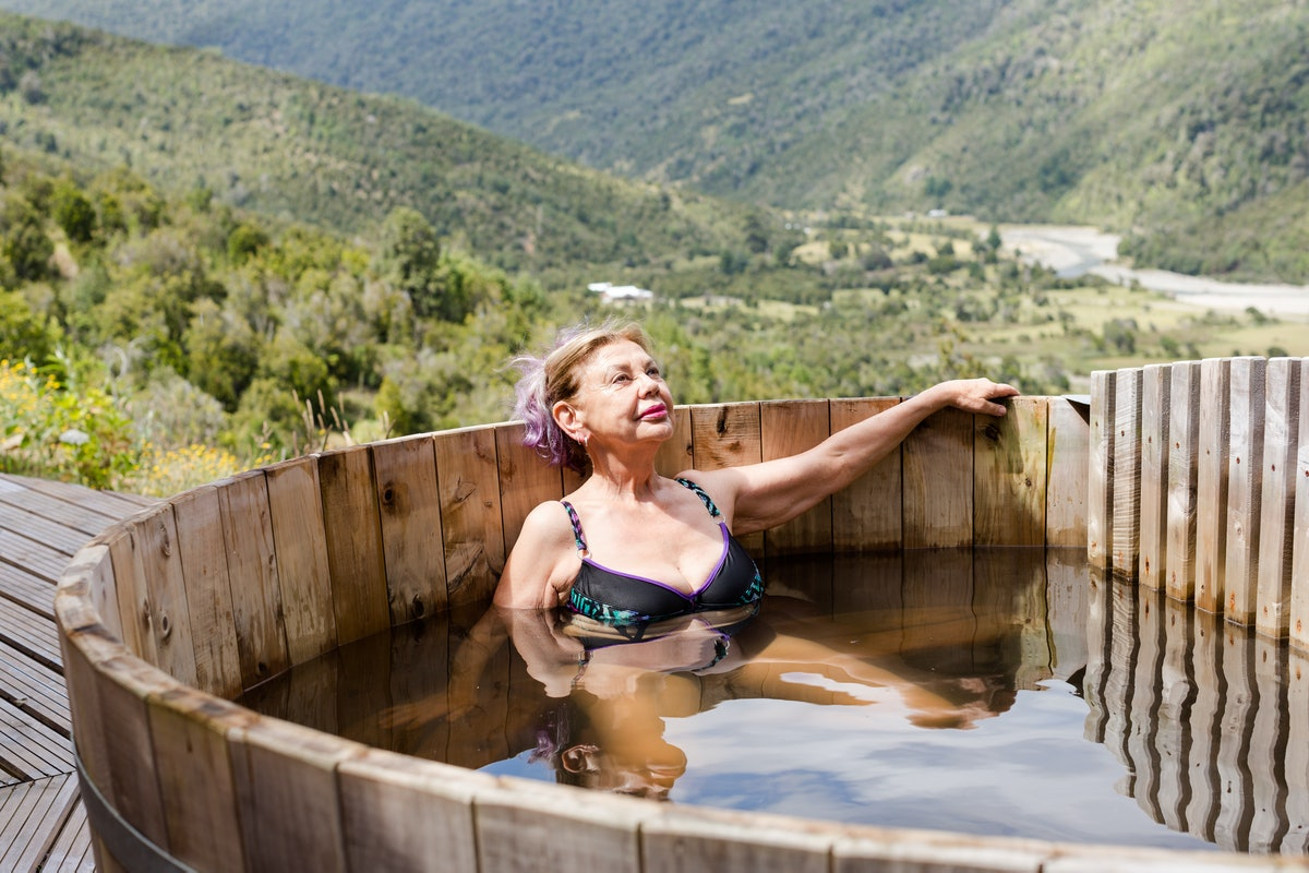 Senior woman relaxing in a wooden hot tub