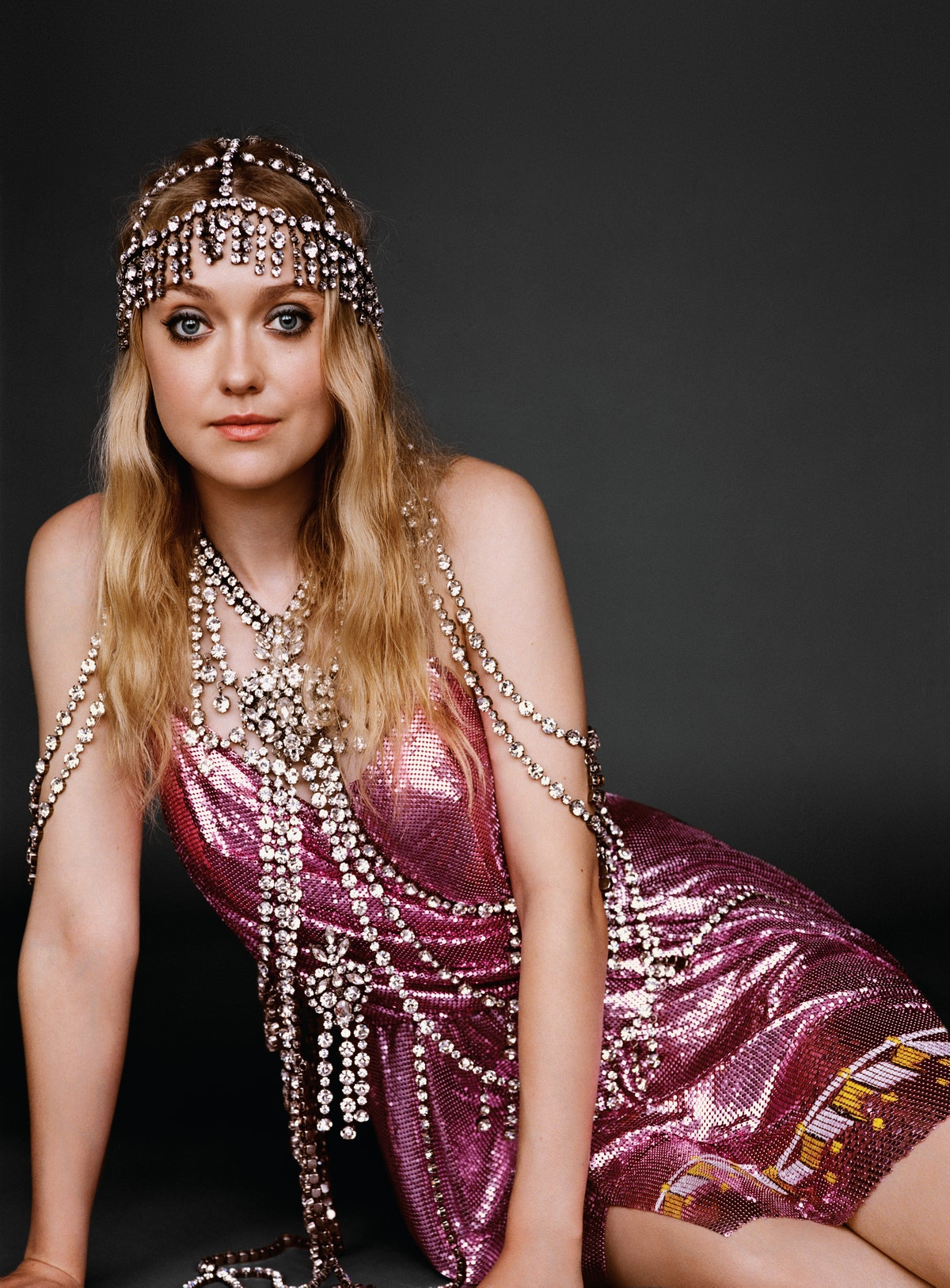 Fanning wears a Gucci dress, headpiece, and body chain.