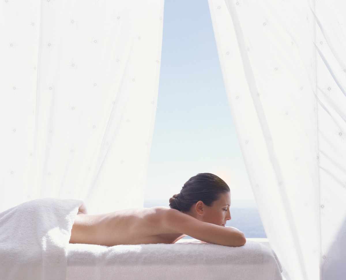 Young woman lying on massage table, eyes closed, profile