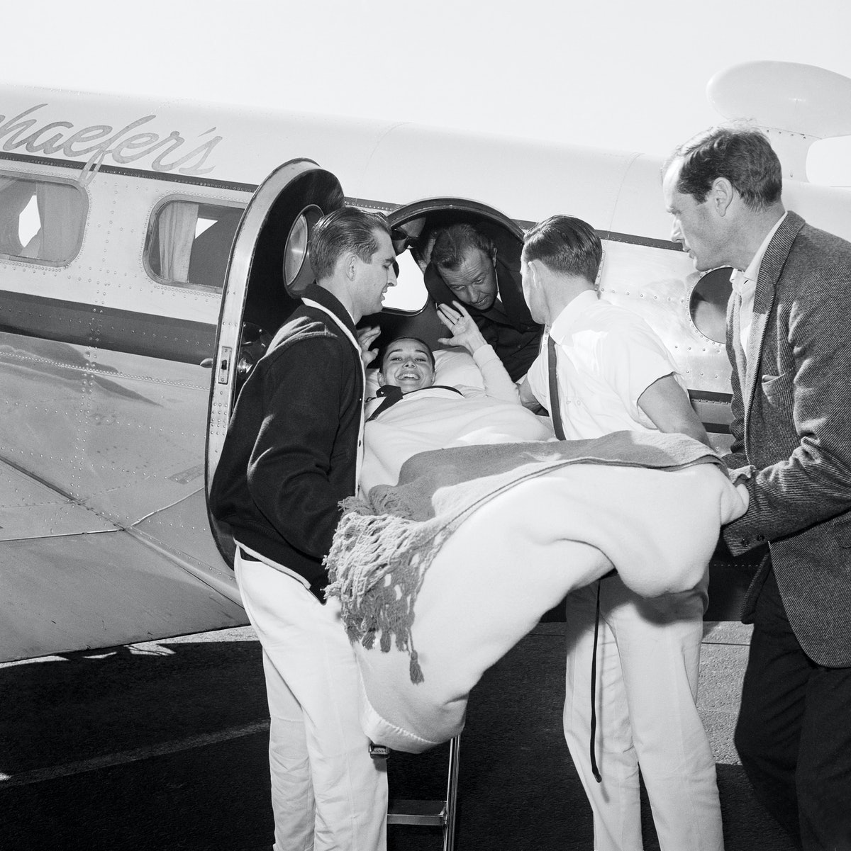 Men Lifting Audrey Hepburn on Stretcher from Airplane