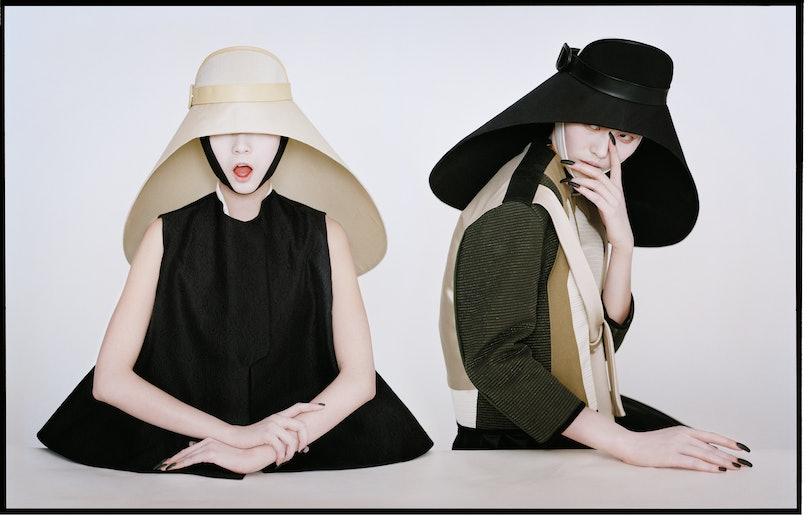 Yves Saint Laurent's lace jacquard vest and habutai silk blouse. Balenciaga by Nicolas Ghesquière hat. Balenciaga by Nicolas Ghesquière's silk dress and hat.