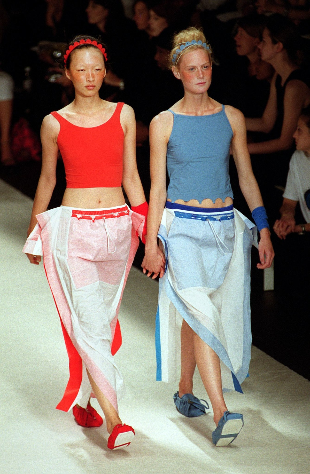 Two models wear red and blue tank tops over white