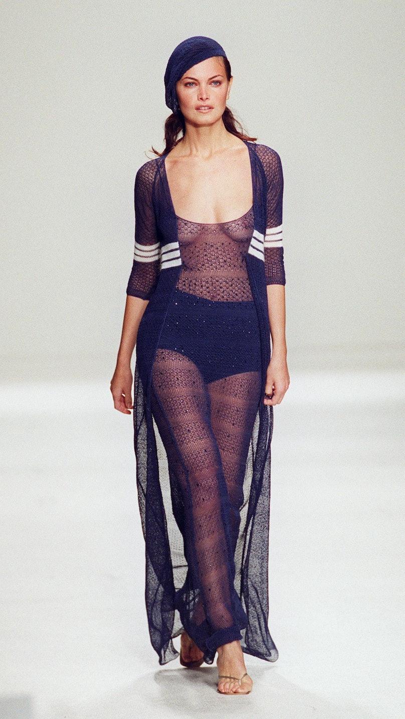 A  model wears a sheer floor-length sweater wrap d