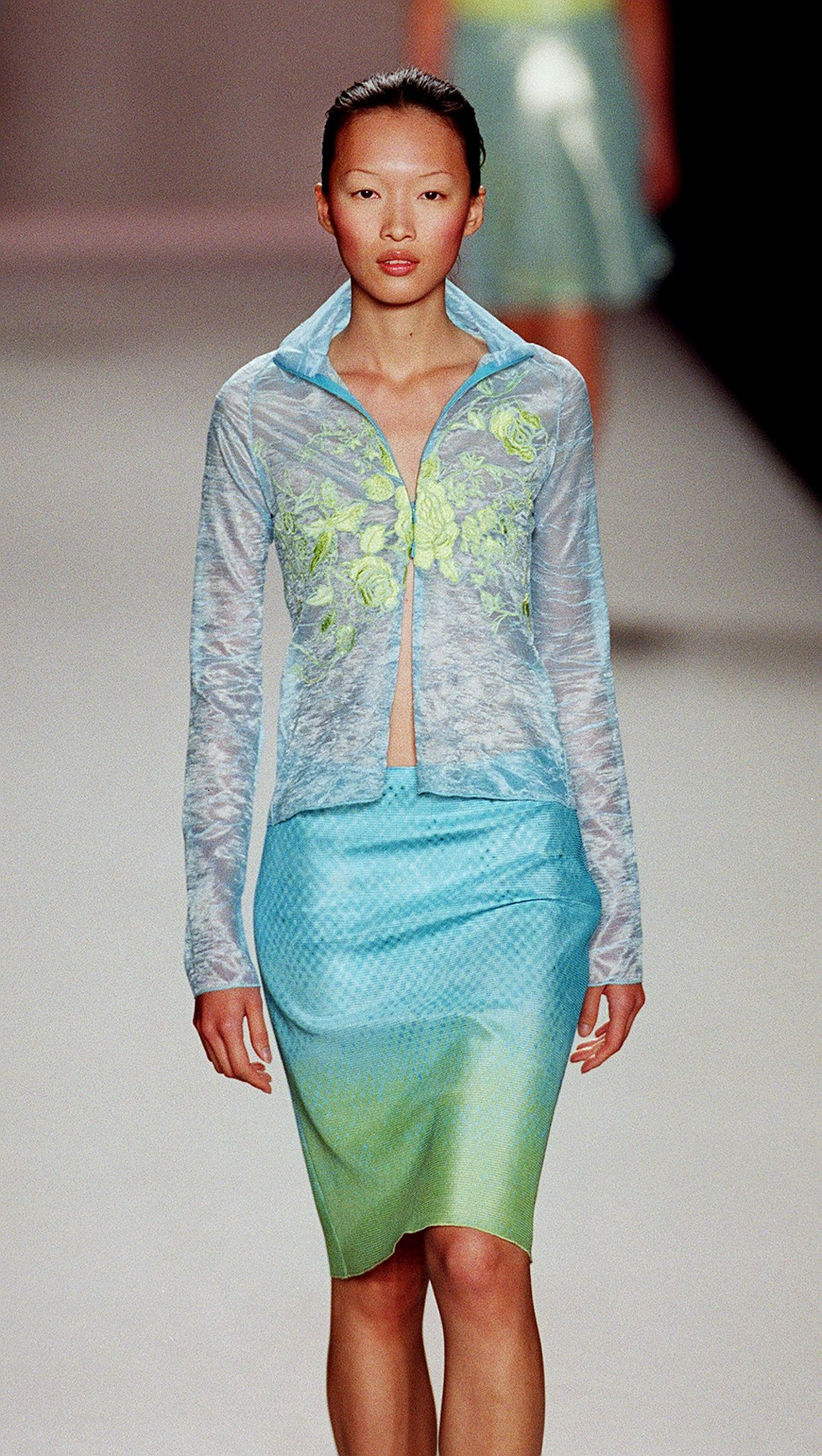 A model wears a print chiffon blouse over a turquo