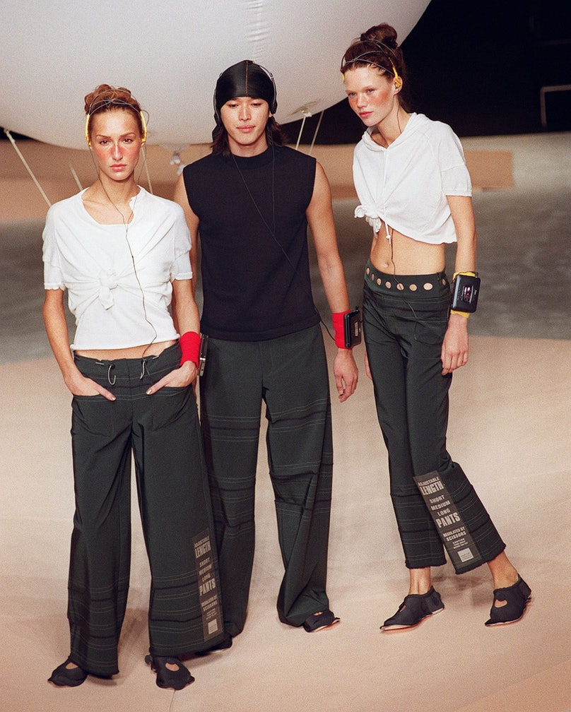 Three models display black and white outfits durin