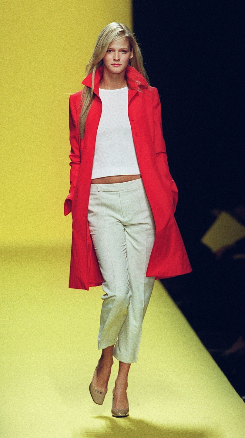 A model wears a red knee-length coat over a white