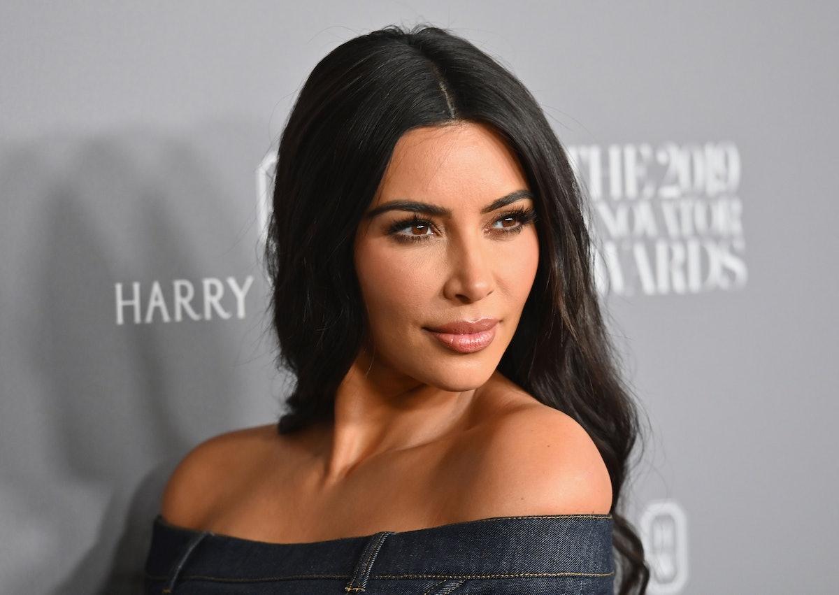 Kim Kardashian strikes a pose on a red carpet.