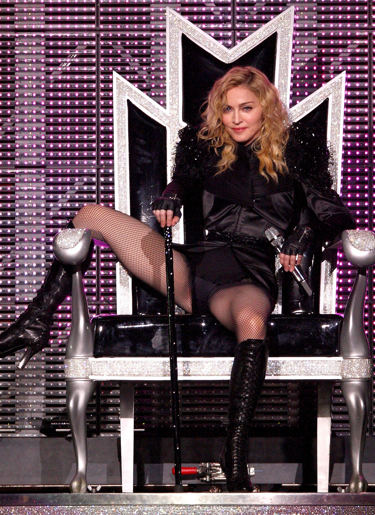 Madonna sits on a throne on stage.