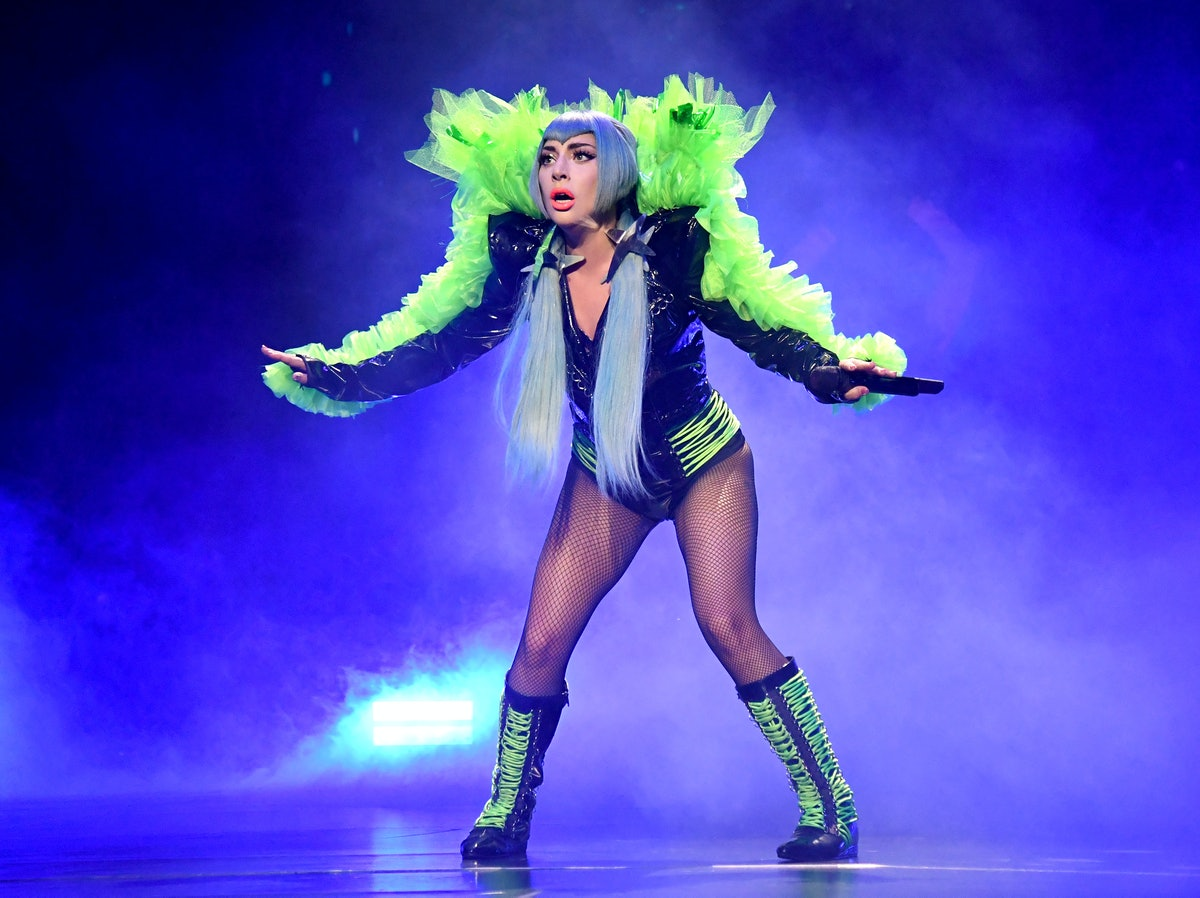 Lady Gaga in concert with green feathers.