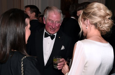 Prince Charles mingling at an event with a drink.
