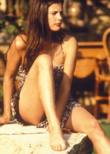 Liv Tyler wearing a dress sitting on a rock on the set of Stealing Beauty in Tuscany.