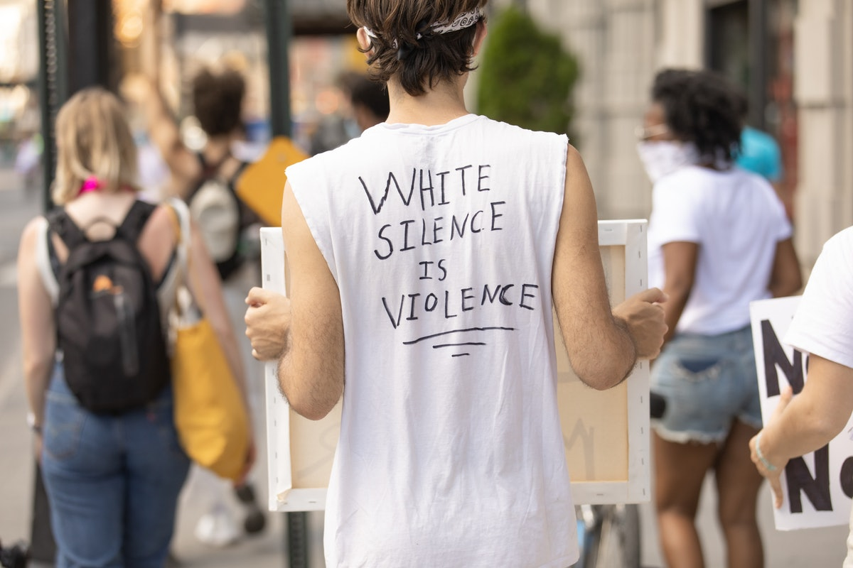 """A person wearing a """"white silence is violence"""" t-shirt"""