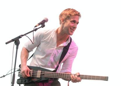Ryan Gosling holds a bass guitar.