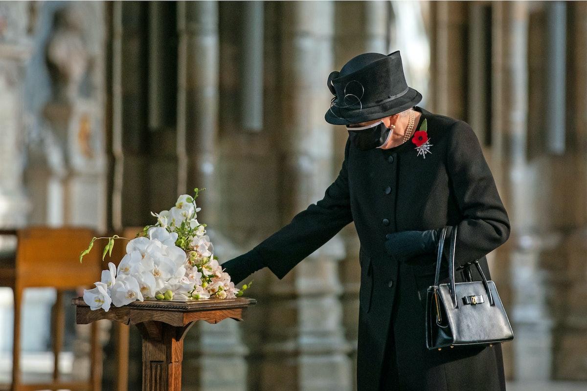 Queen Elizabeth II touching flowers in a face mask