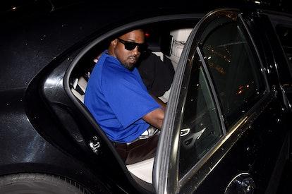 kanye in a car wearing sunglasses