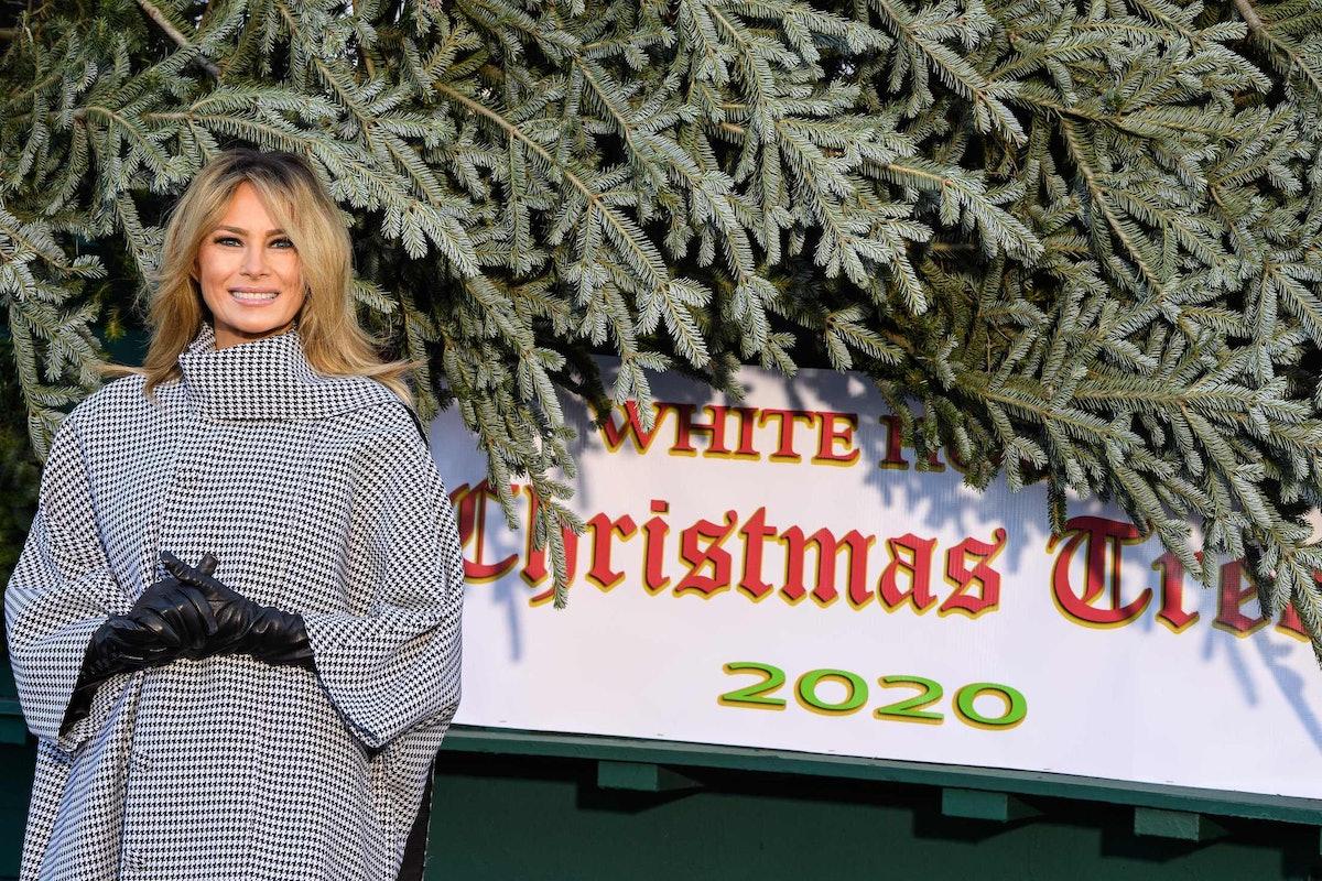 Melania Trump smiling next to a Christmas tree