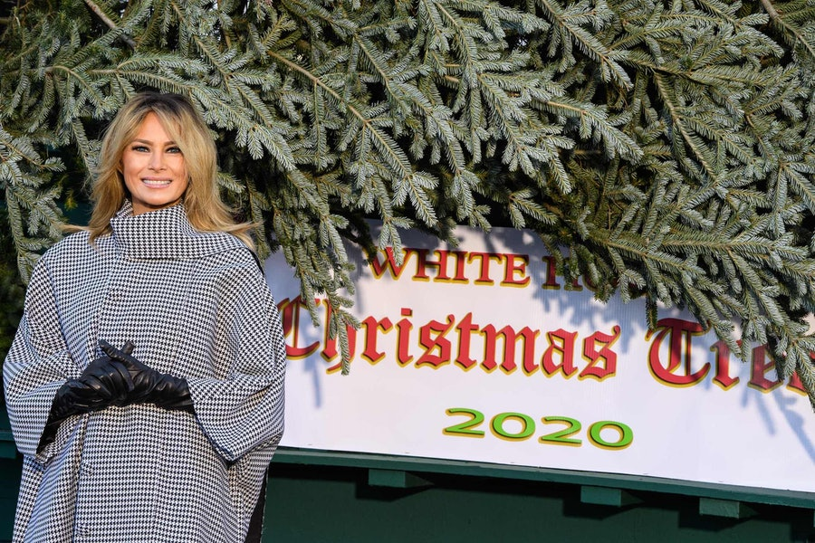 Melania Trump smiling next to a Christmas tree