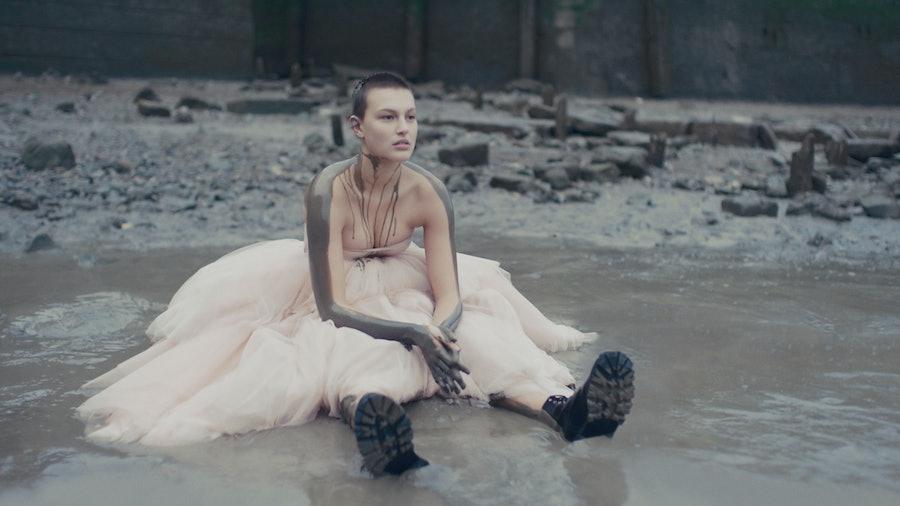 An Alexander McQueen model sitting in mud