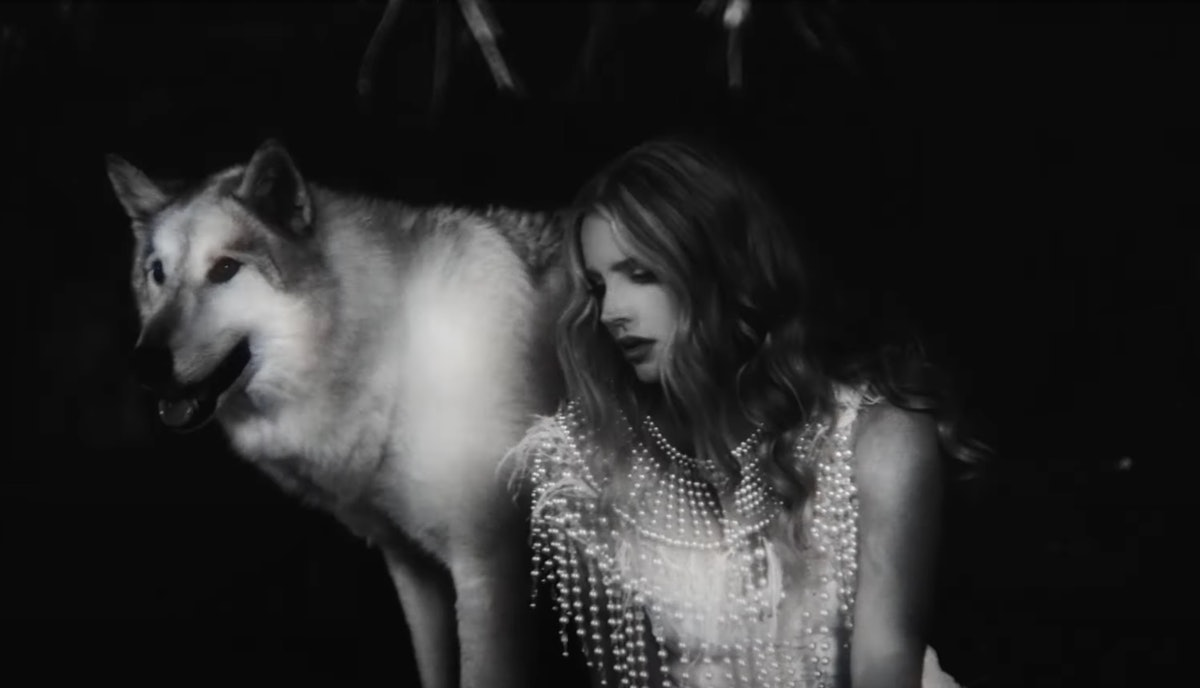 Lana Del Rey and a white wolf.