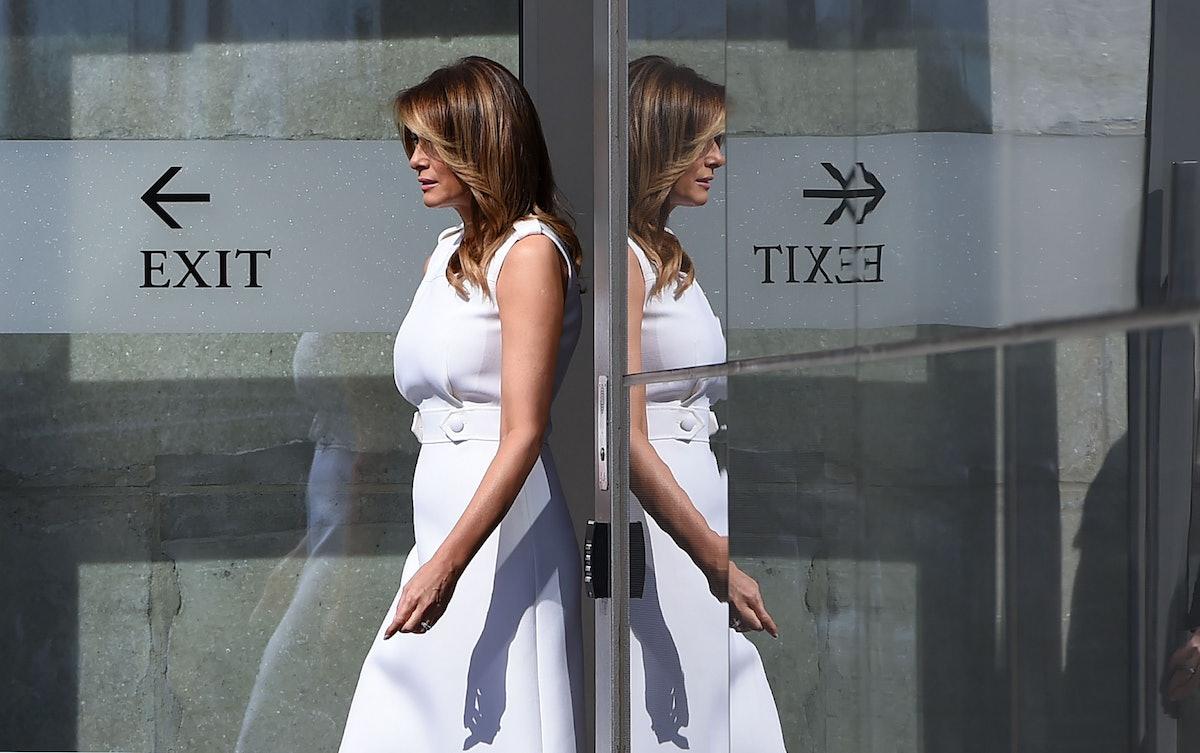 Melania Trump walks out a door.