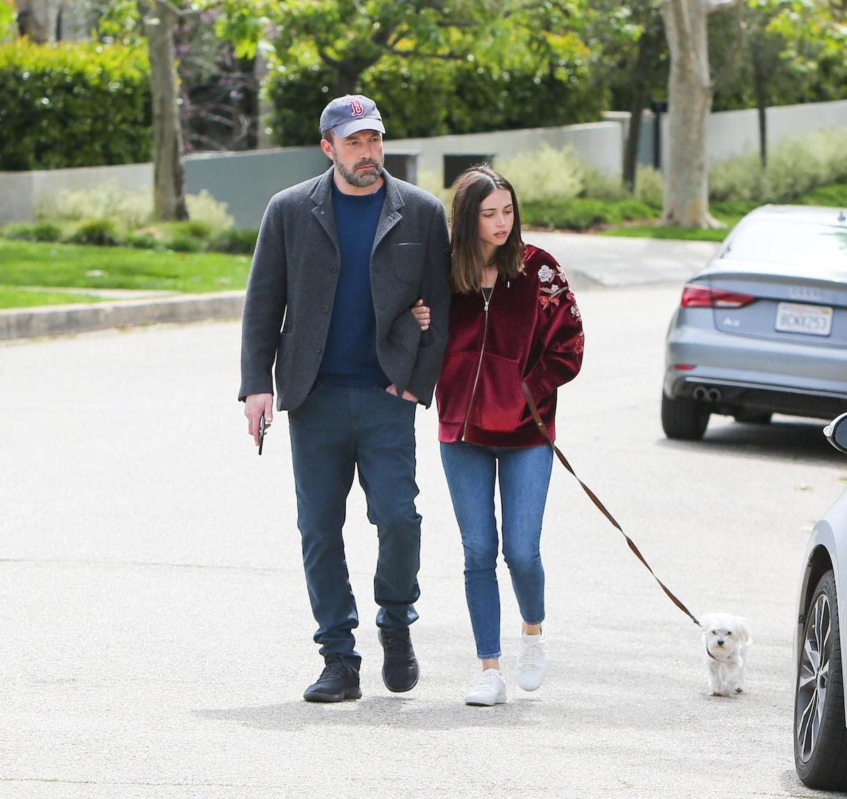 Ben Affleck and Ana De Armas walking a dog.