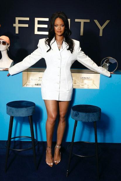 Rihanna posing against a Fenty backdrop