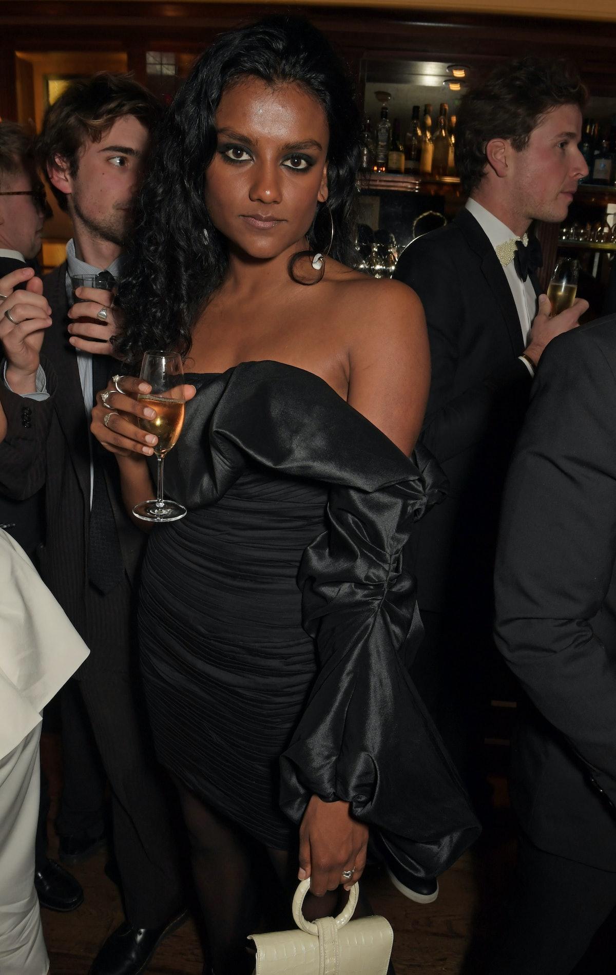 Simone Ashley in a black dress.