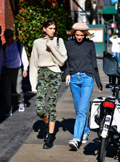 While taking a stroll with her companion in New York City, Kaia Gerber wore a chunky knit sweater from H&M, which she then paired with some cropped camo pants from Nili Lotan.