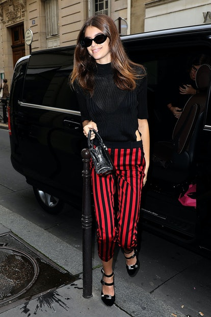 Kaia Gerber goes shopping in Paris, France while wearing an iconic outfit that included pair or red stripe trousers from The Kooples.